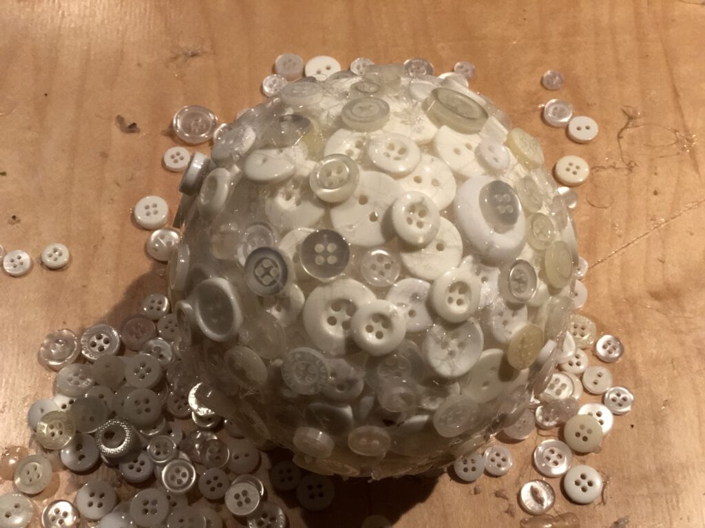 Easy Christmas tree ornament diy made out of buttons that are layered on the styrofoam ball