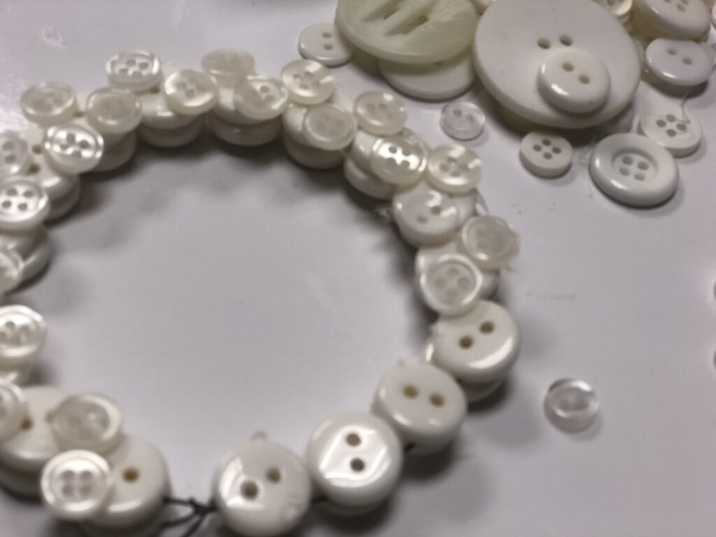 White buttons on the thin wire to form mini Christmas wreath. Layered buttons Christmas ornament DIY