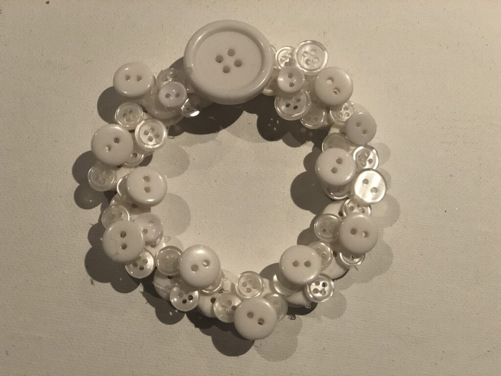 White buttons on the thin wire to form mini Christmas wreath. Layered buttons  wreath Christmas ornament DIY