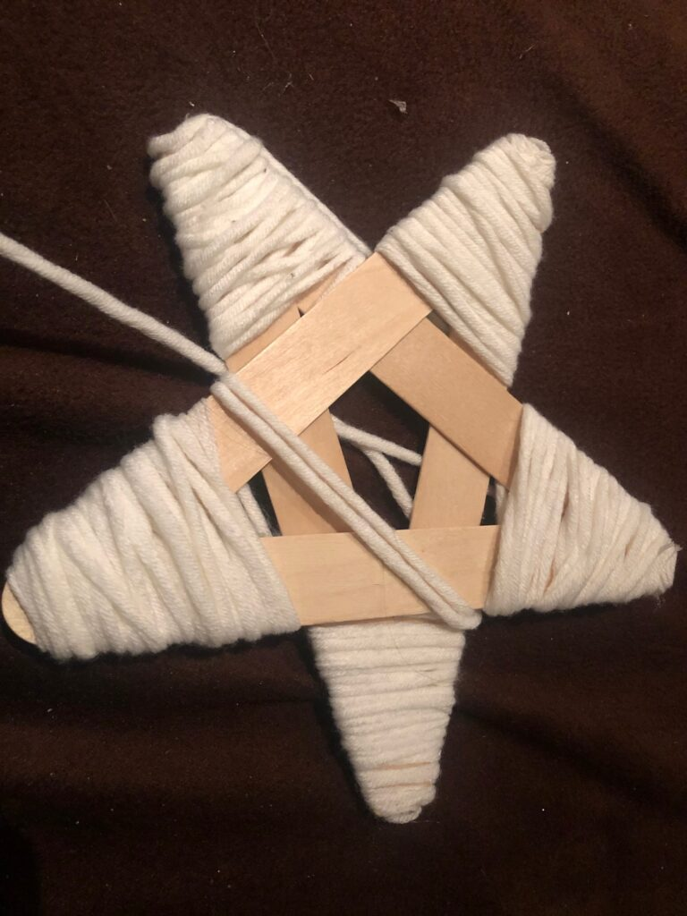 White yarn wrapped around star made out of Popsicle  sticks