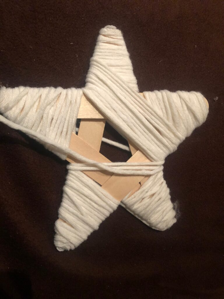 star tree topper made out of Popsicle sticks wrapped with white yarn